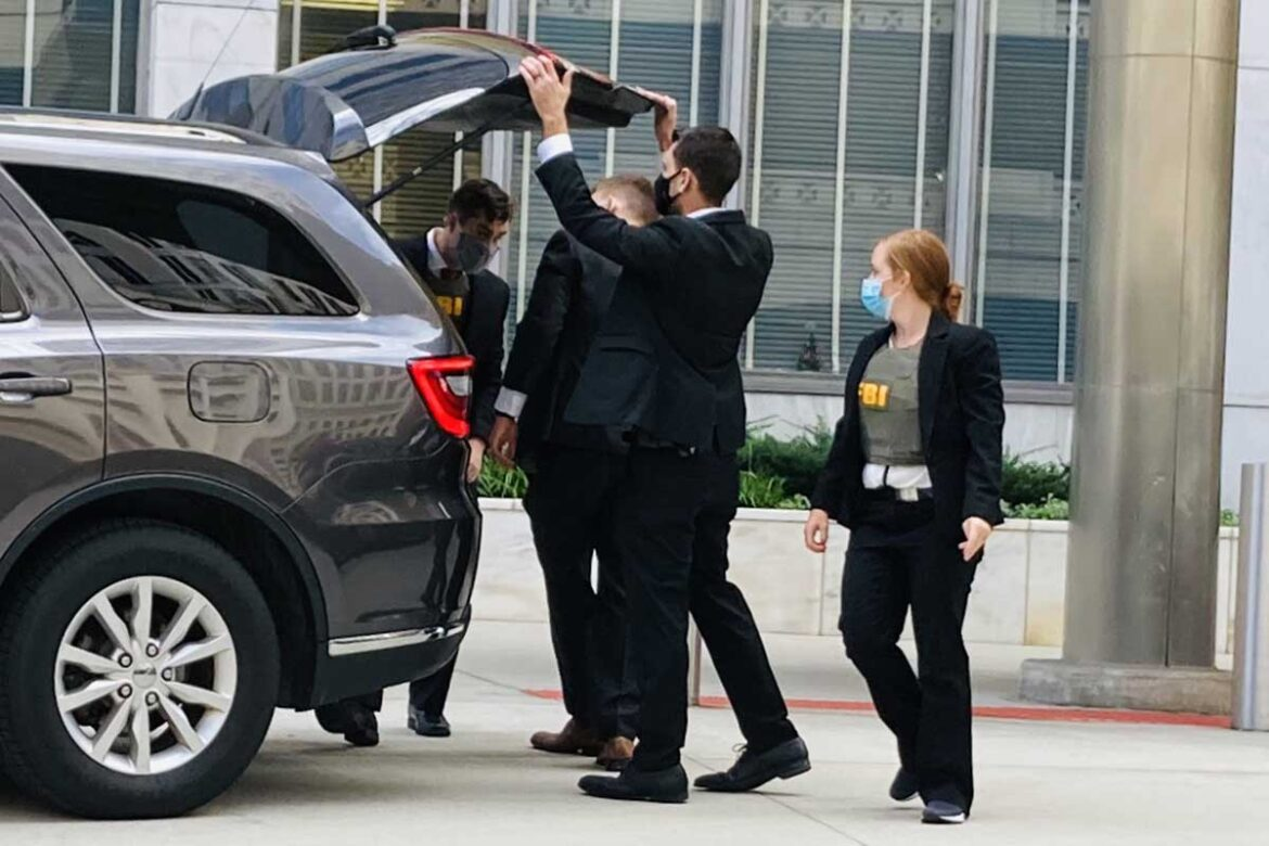 Federal agents haul away boxes into car